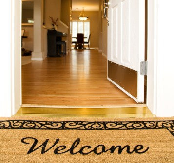 Image of a clean home. Front door open with welcome mat.